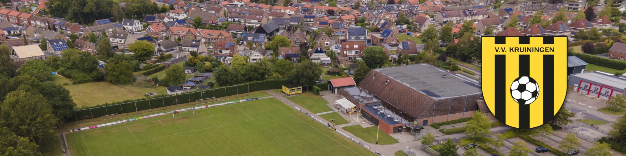 Een dronefoto van het hoofdveld van voetbalvereniging Kruiningen met het dorp Kruiningen op de achtergrond