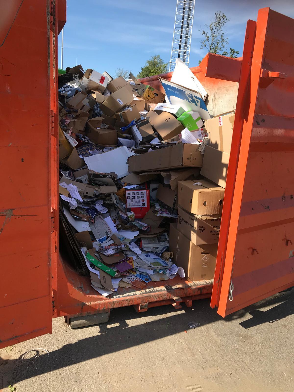 Een vuilcontainer met oud papier